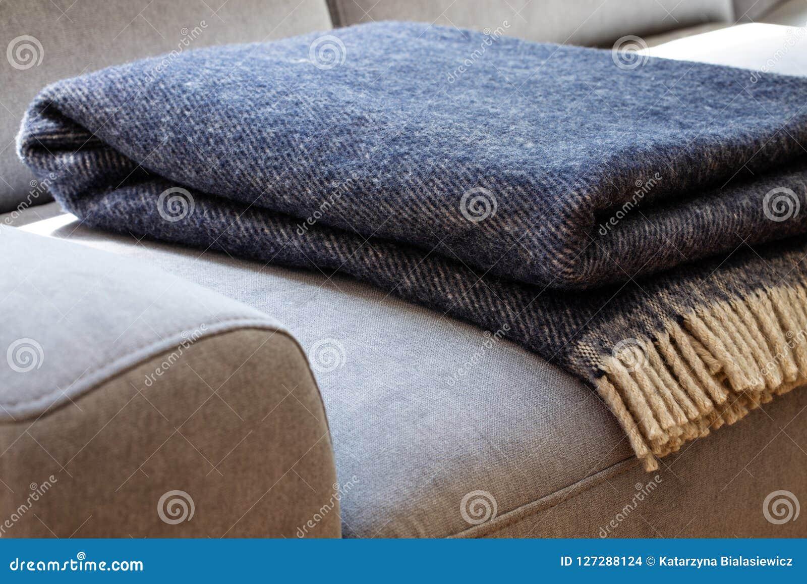 Close-up van een warme, marineblauwe, woldeken met beige rand op een bank op z n gemak, grijze in een comfortabel woonkamerbinnen