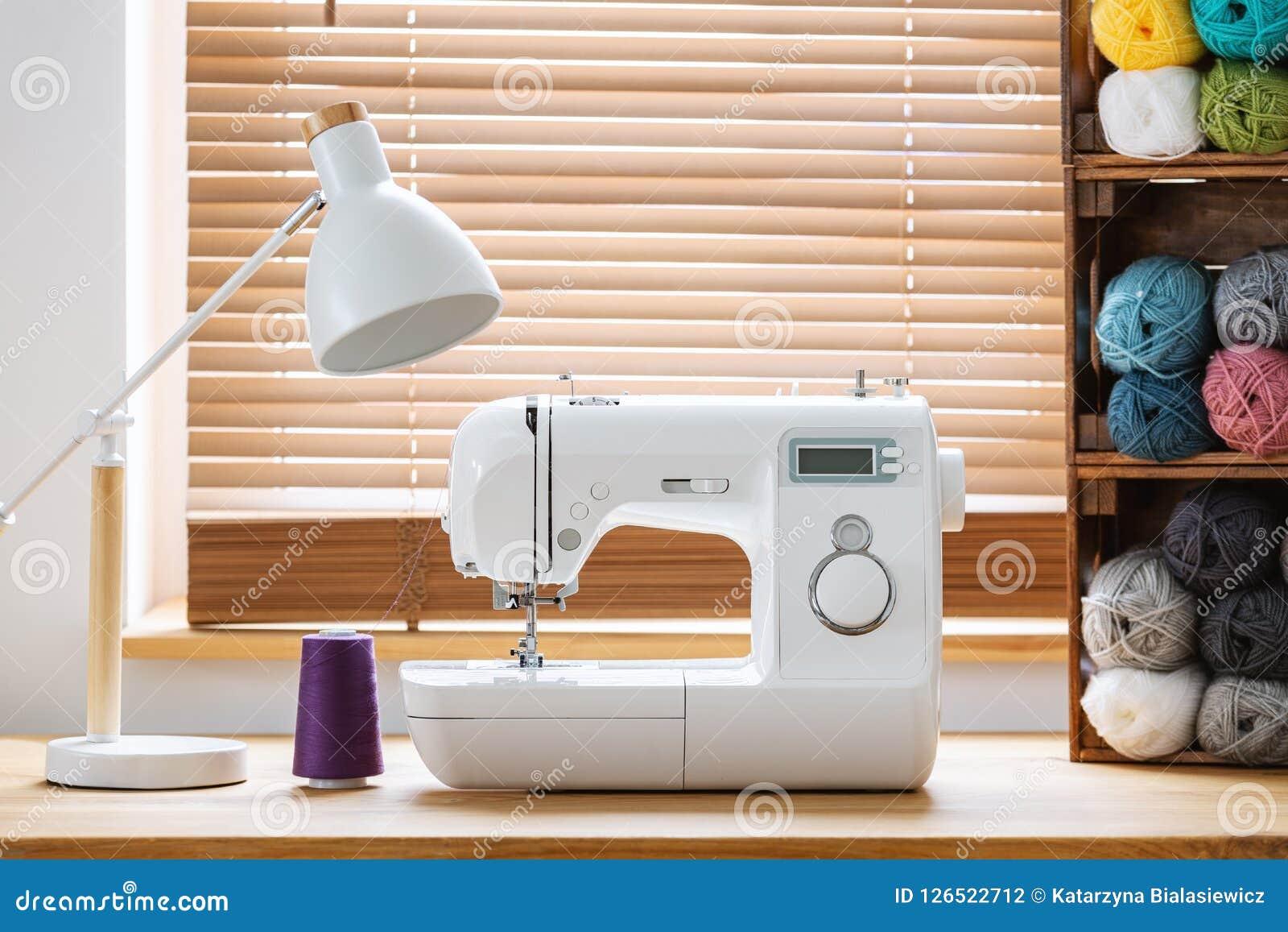 Close-up van een witte naaimachine met een purpere draad en kratten met garen door een venster in een helder binnenland van de am