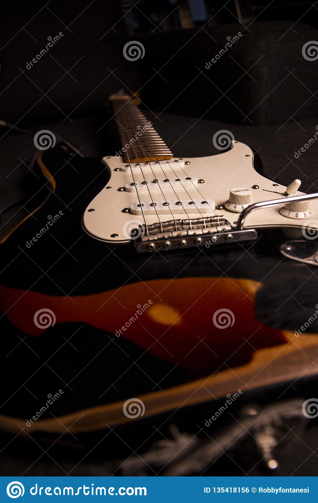 Close-up van een zonnestraal-gekleurde elektrische die gitaar met zwarte die verf wordt behandeld op bepaalde punten wordt verwij