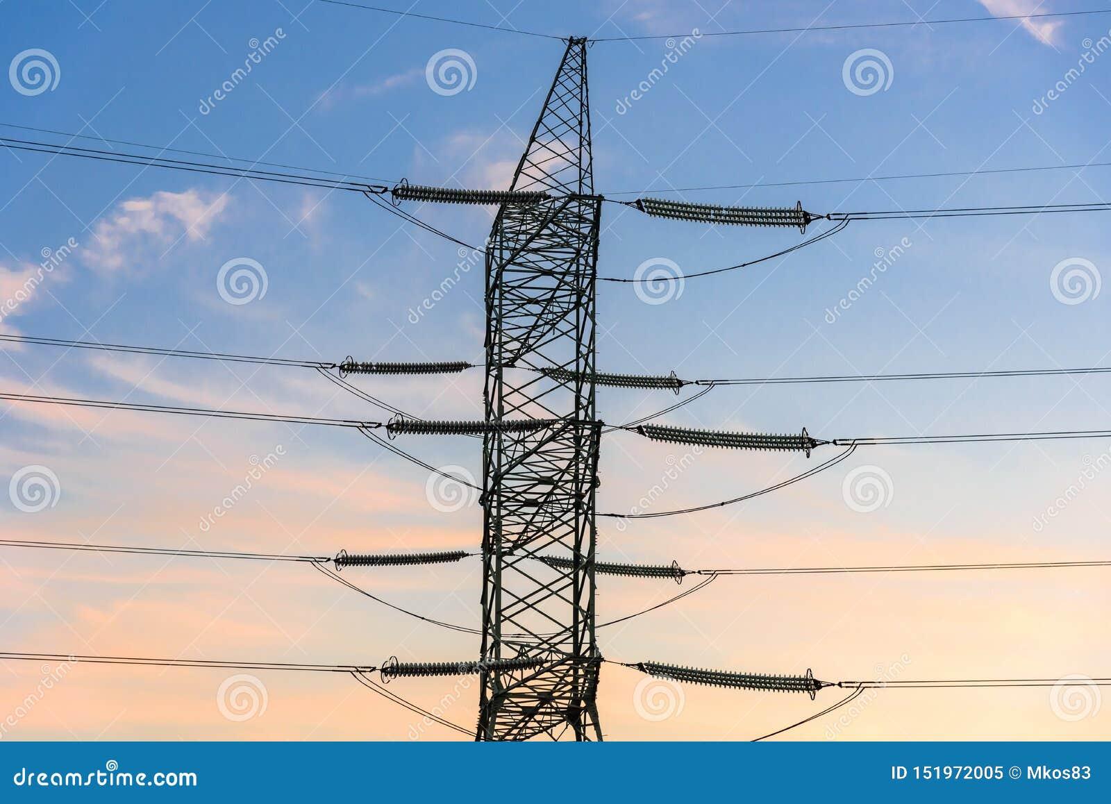 Close-up van elektriciteitspyloon en lijnen bij zonsondergang