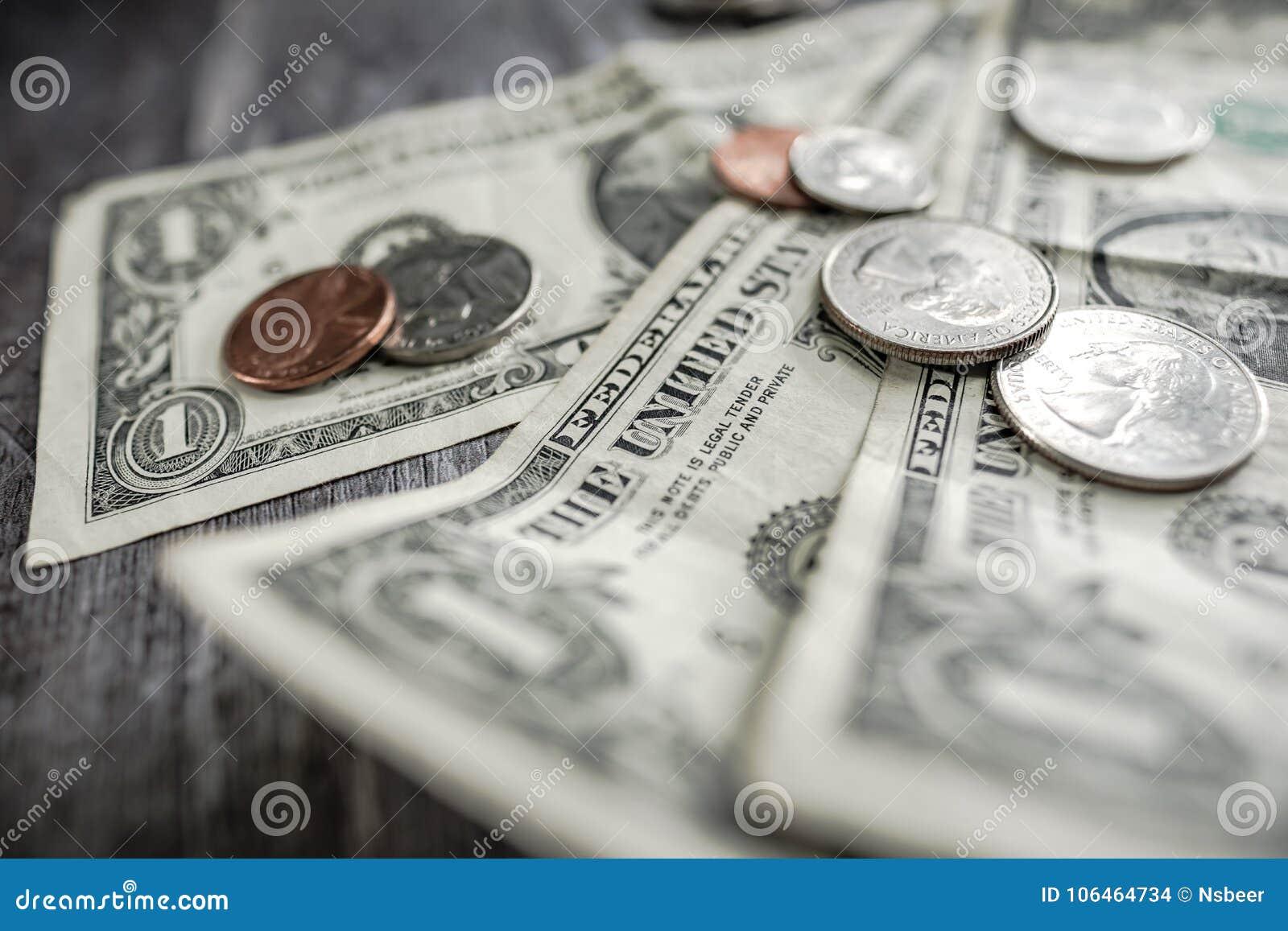 Close-up van gebruikte Amerikaanse die bankbiljetten en het munten op een houten bureau worden gezien