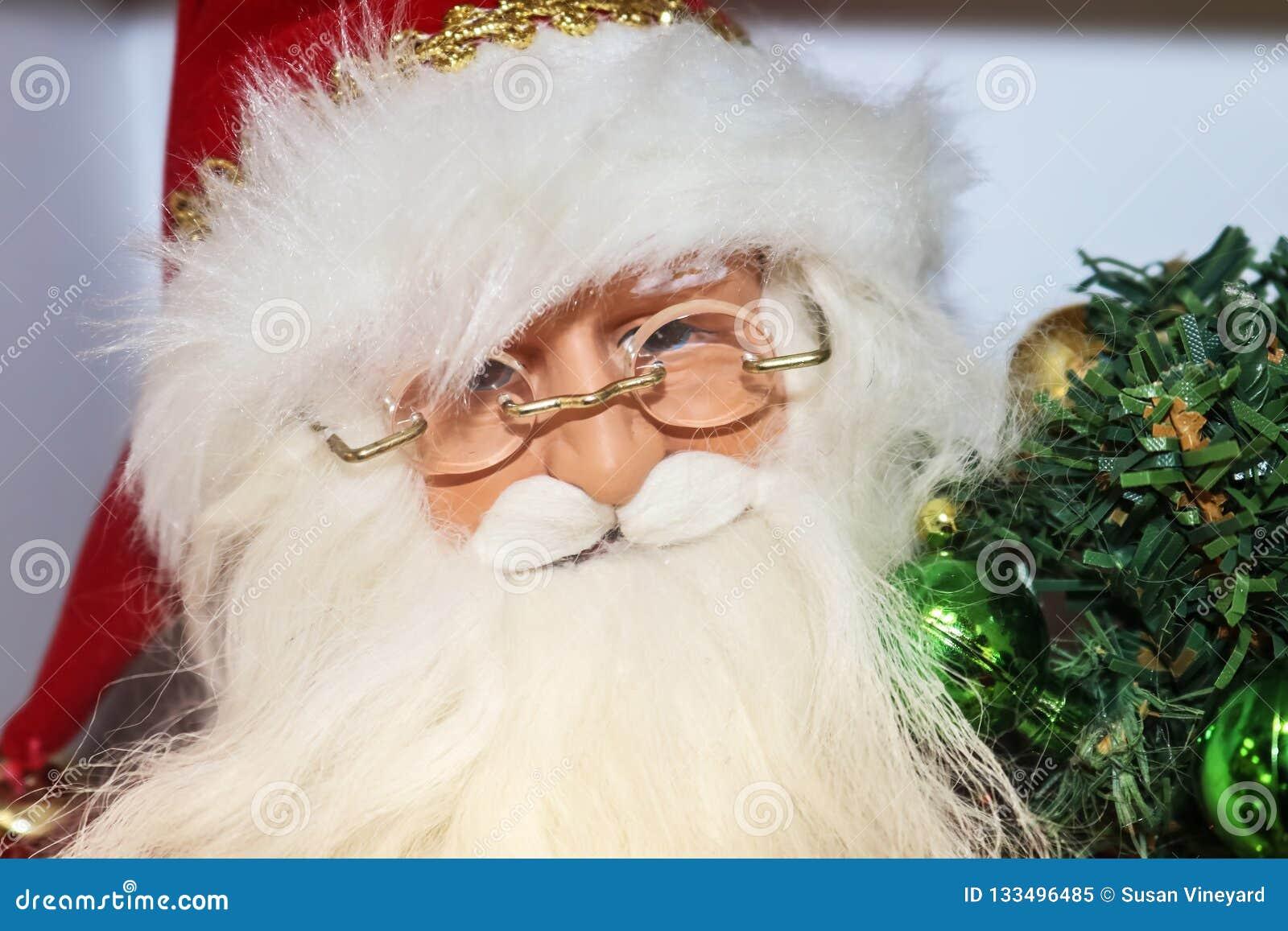 Close-up van gezicht van Santa Claus-het decor van beeldjekerstmis met glazen en met dichtbegroeide baard die groene decoratie ho