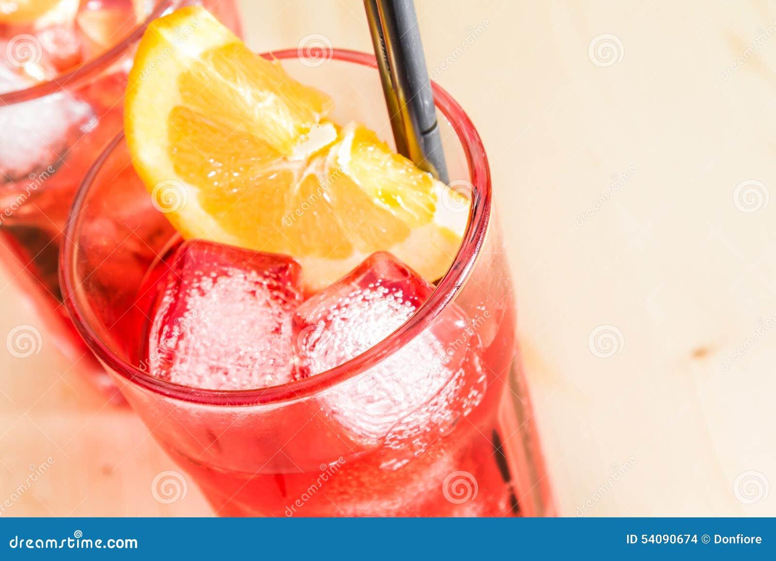 Close-up van glas van aperolcocktail van het spritzaperitief met oranje plakken en ijsblokjes