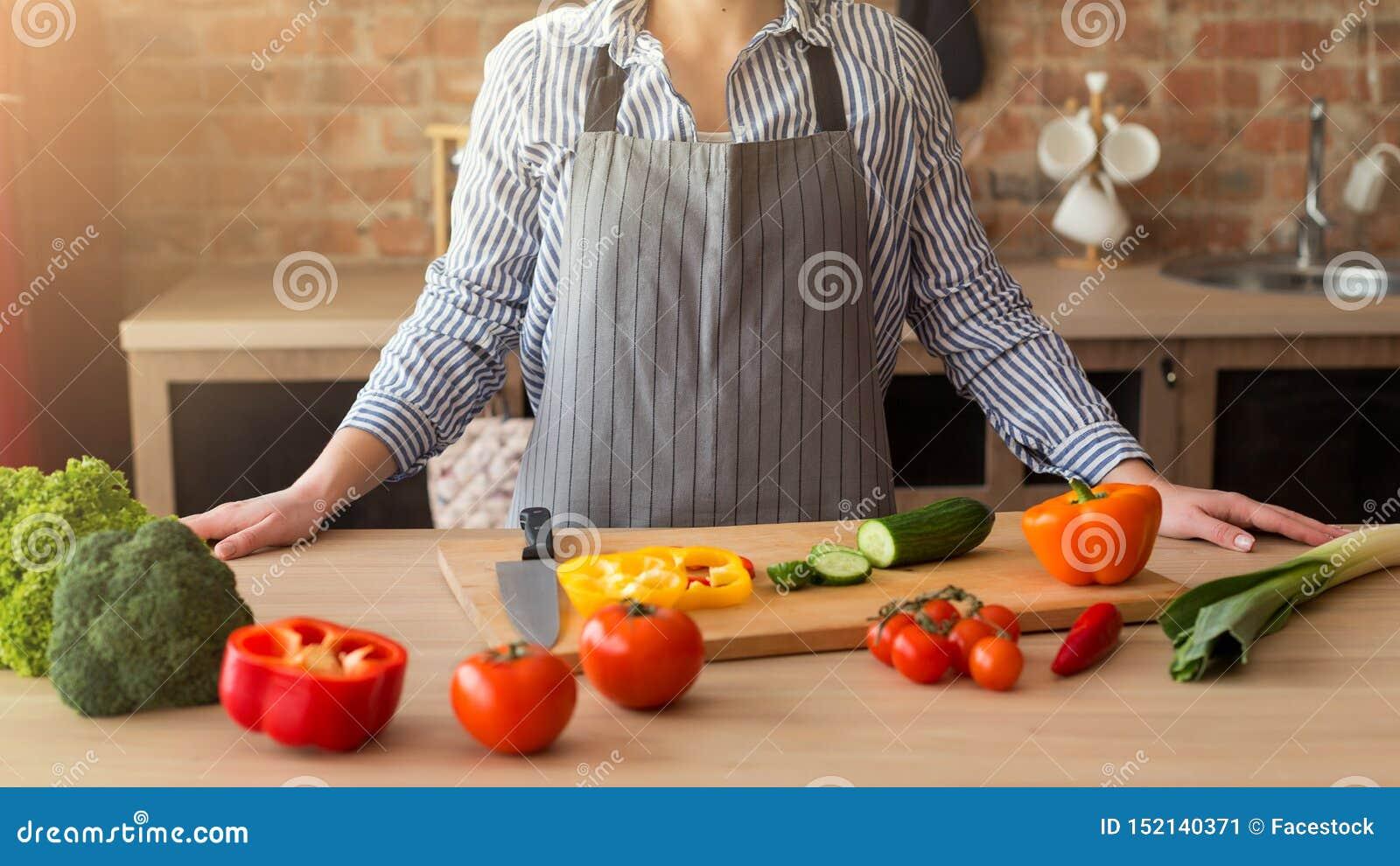 Close-up van handen van de scherpe groenten van de chef-kokkok op houten lijst