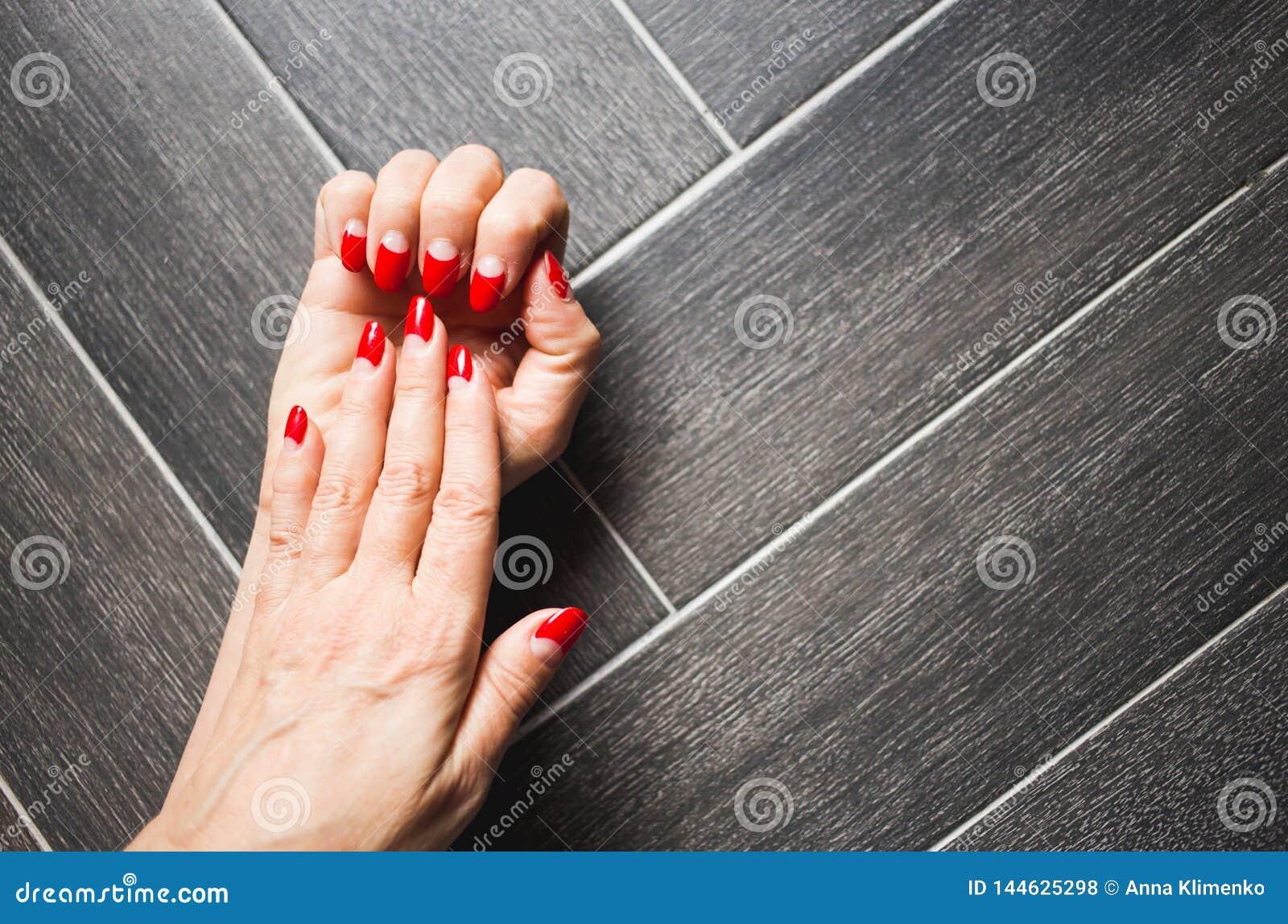Close-up van handen van een vrouw met donkerrode manicure op spijkers tegen donkere houten achtergrond