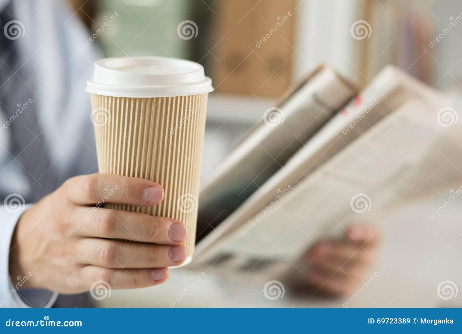 Close-up van het nieuws en de holdingskoffiekop van de zakenmanlezing