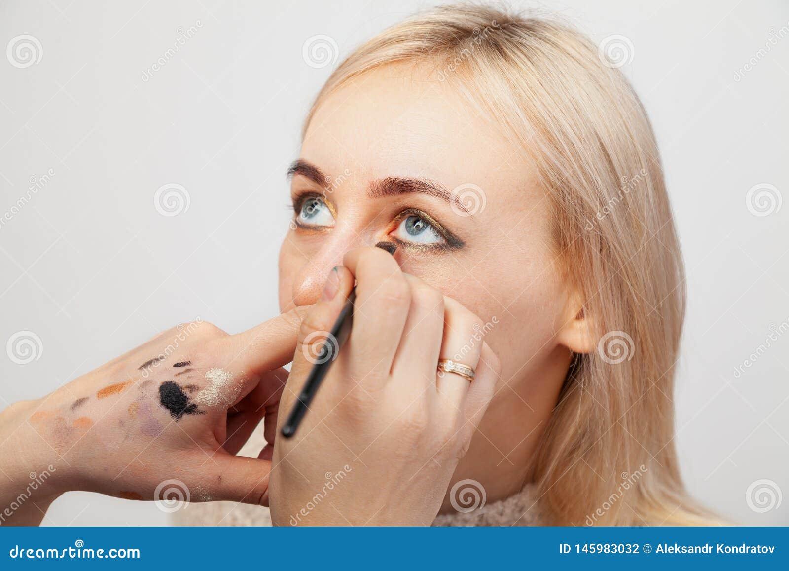 Close-up van het toepassen van samenstelling in de salon op het model met geopende ogen in de oosterse stijl, de kunstenaar die g