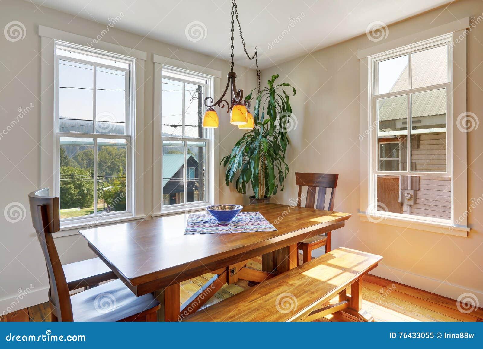 Close up van houten eettafel met twee stoelen en bank stock