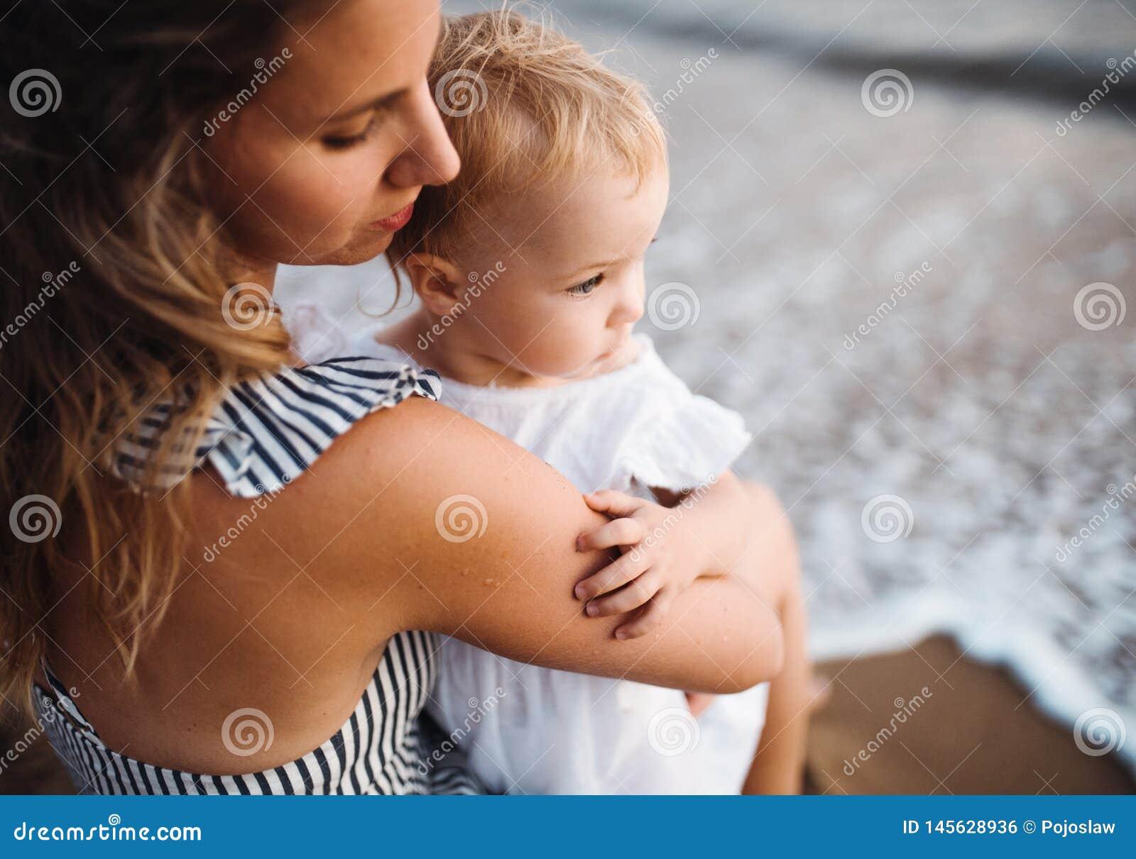 Close-up van jonge moeder met een peutermeisje op strand op de zomervakantie
