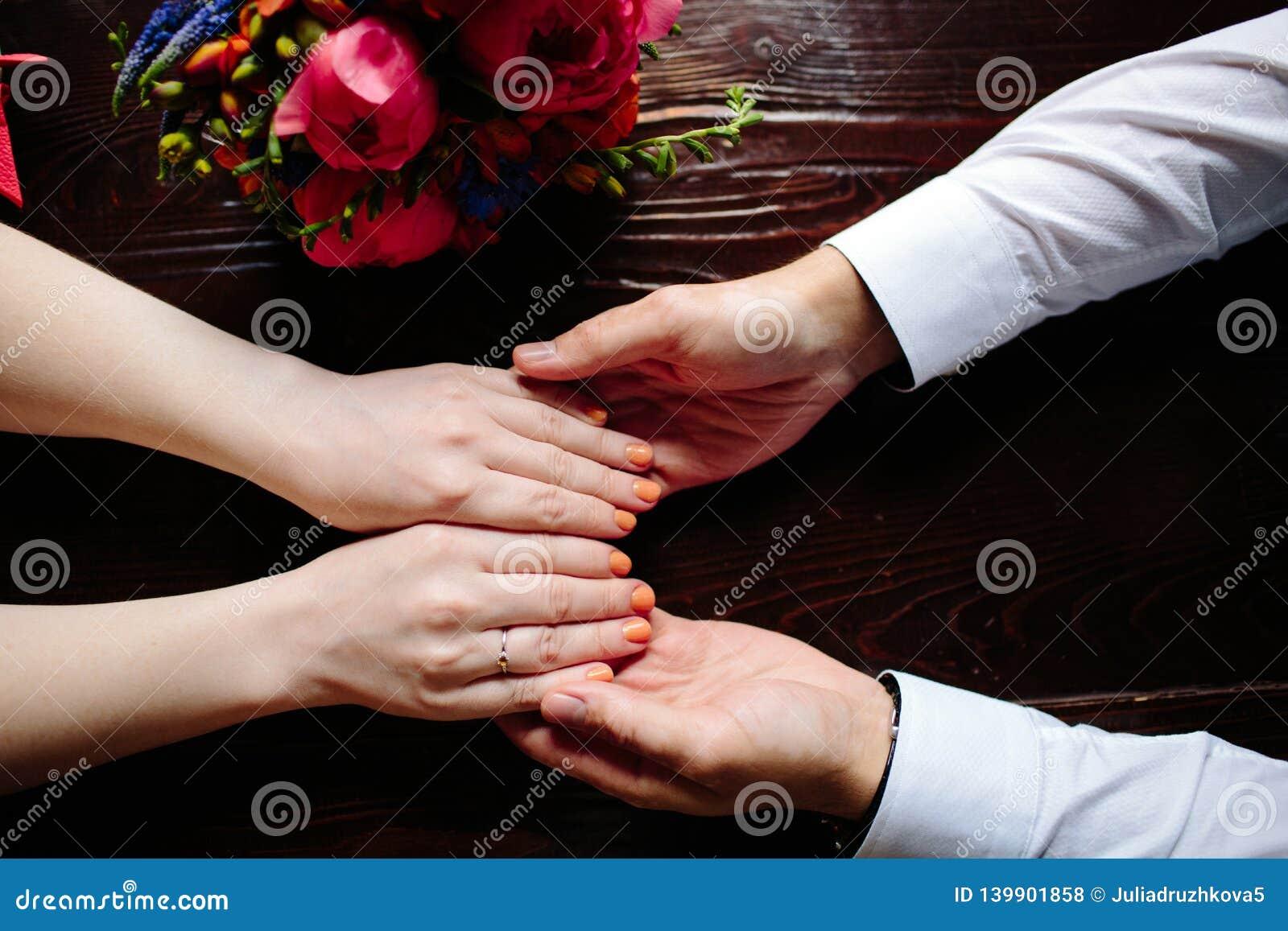 Close-up van man en vrouwenholdingshanden terwijl het kruising van de kreek Nadruk op handen van paar