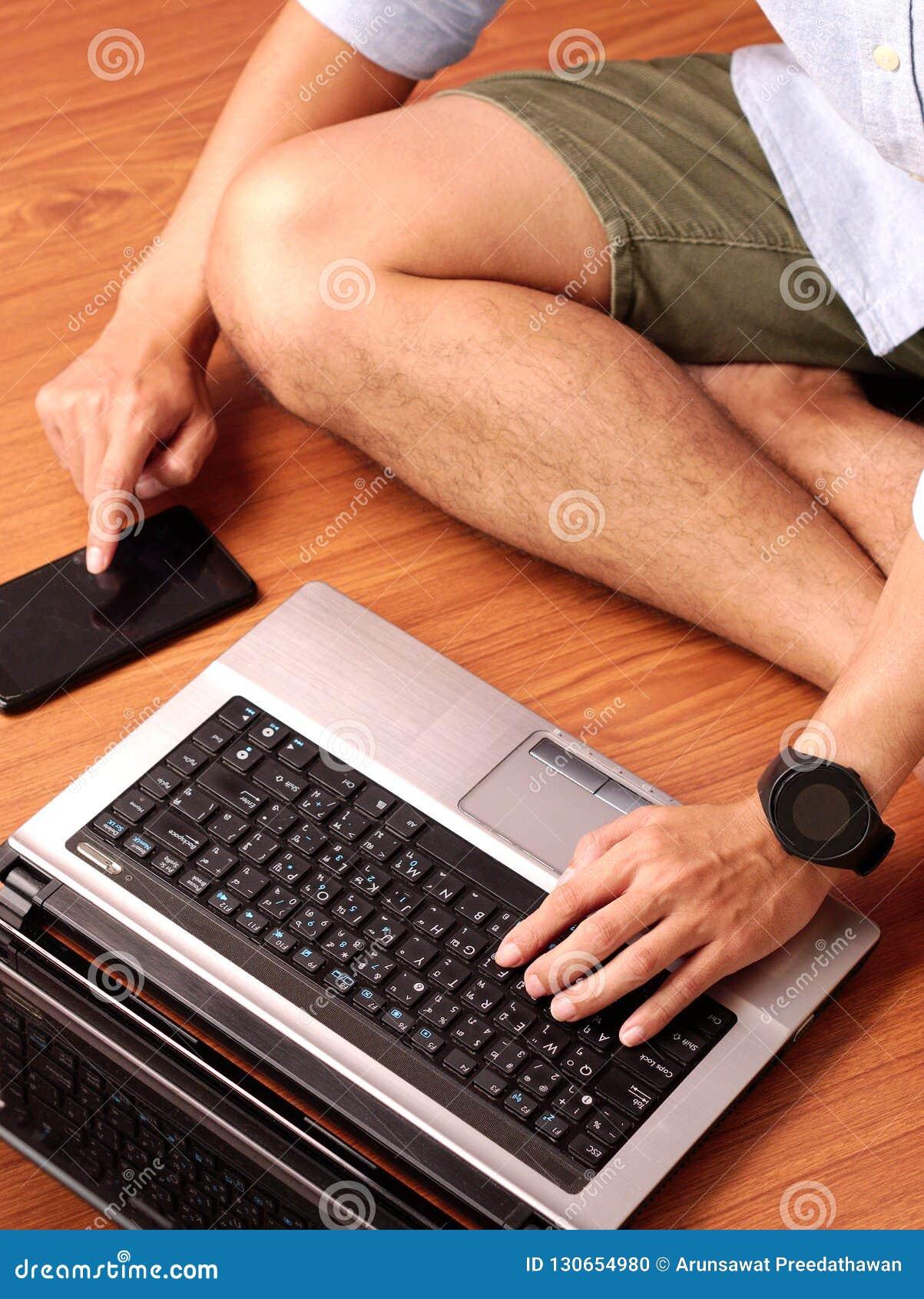 Close-up van mensenzitting het typen op keybord van zijn laptop en zijn smartphone gelijktijdig