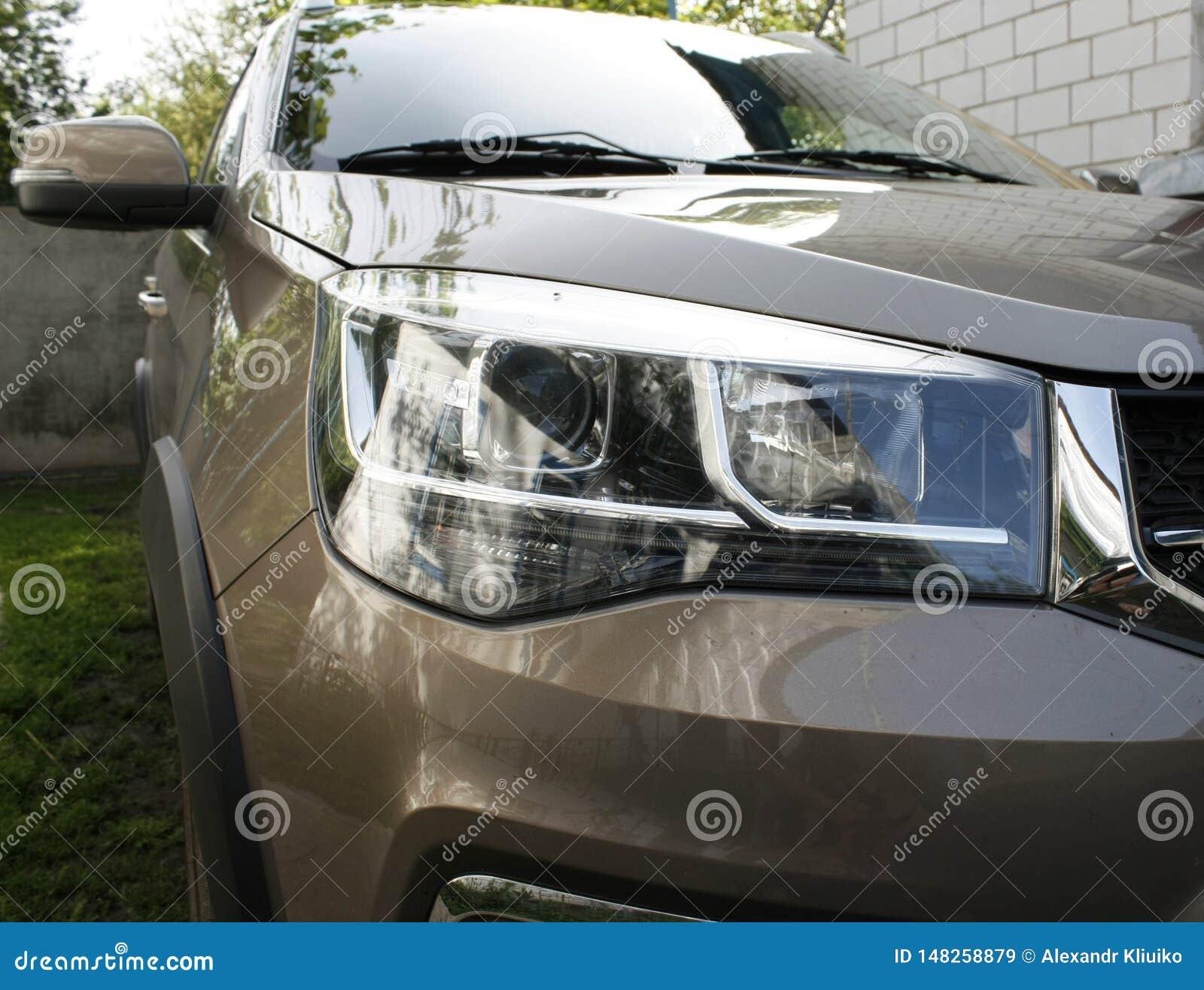 Close-up van moderne automobiel LEIDENE koplampen in openlucht op een bruine auto van een Chinese fabrikant