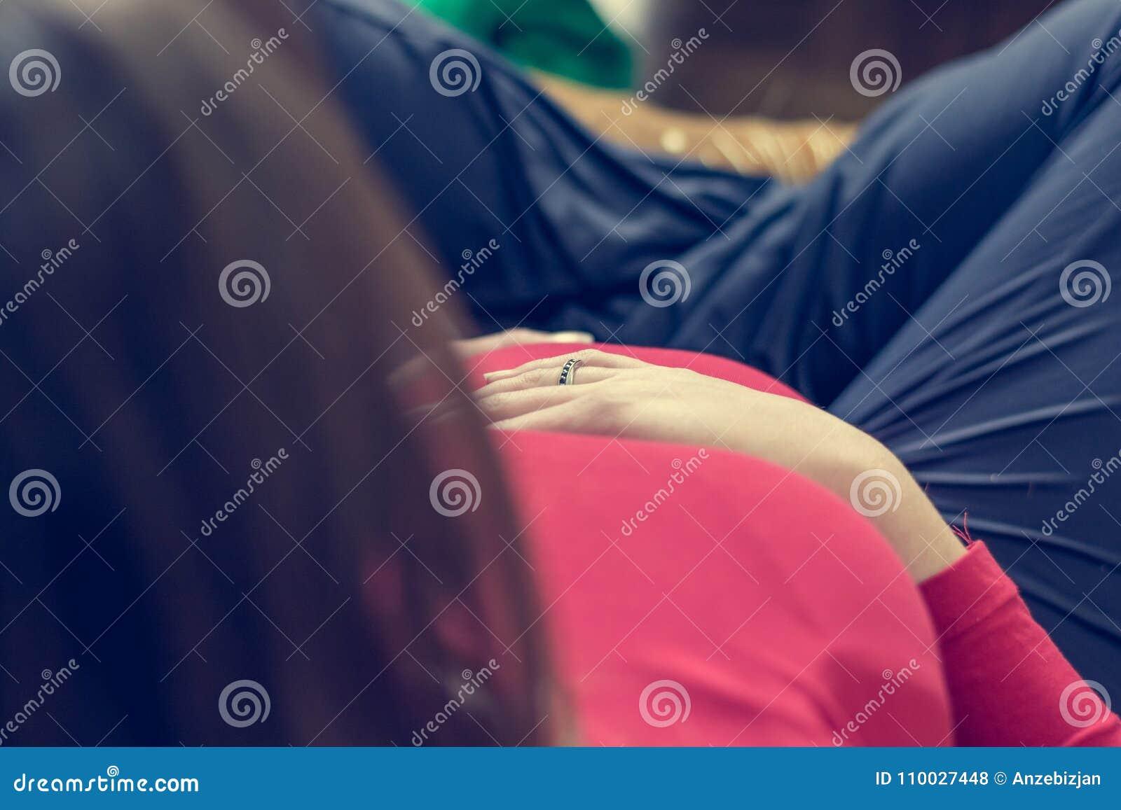 Close-up van moeder die haar zwangere buik houden