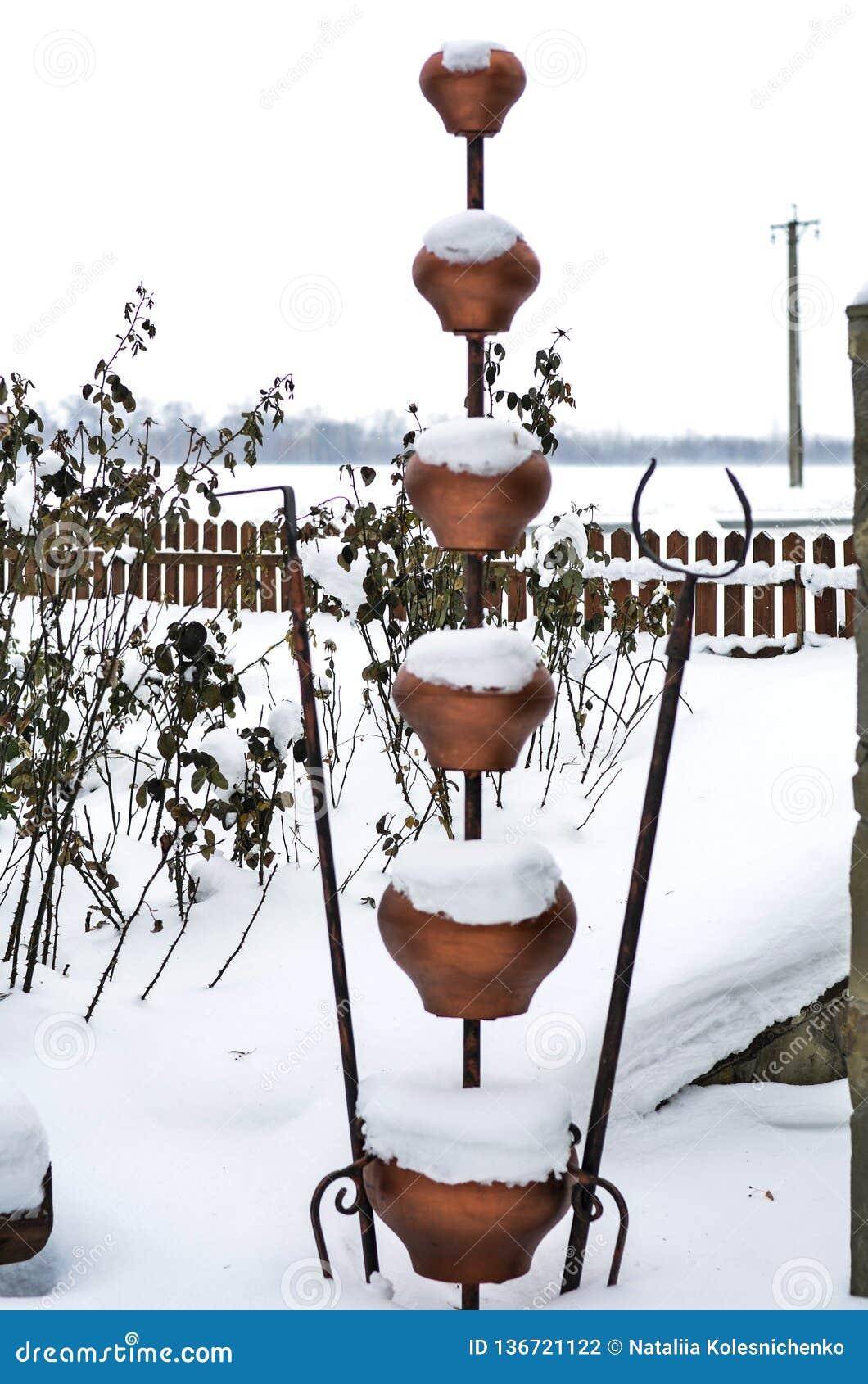 Close-up van oude kleidippers van diverse grootte met een mooi de winterlandschap op de achtergrond
