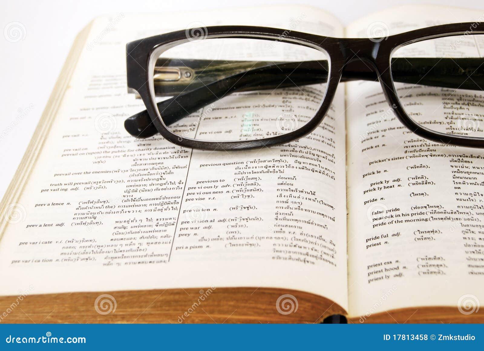 Close-up van oude woordenboek en glazen