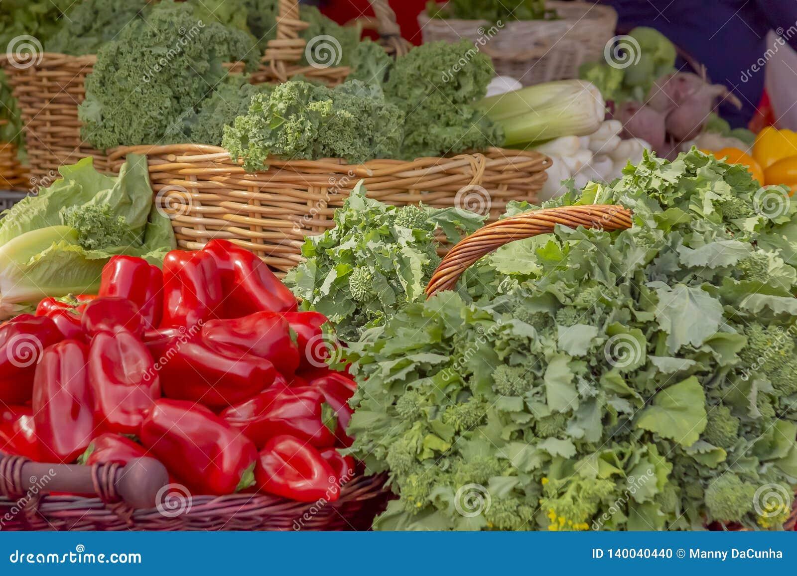 Close-up van rijke rode groene paprika s met een verity van groene die groente bij de groene markt wordt getoond