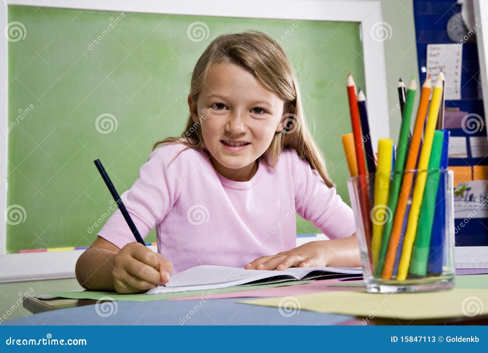 Close-up van schoolmeisje het schrijven in notitieboekje