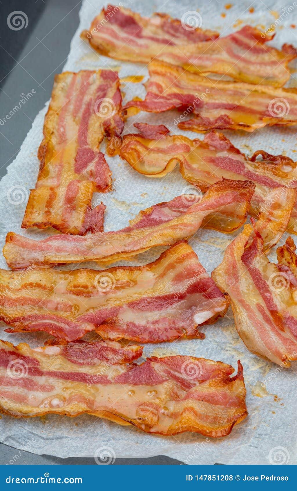 Close-up van smakelijke plakken van gerookt bacon Ge?soleerdj op witte achtergrond