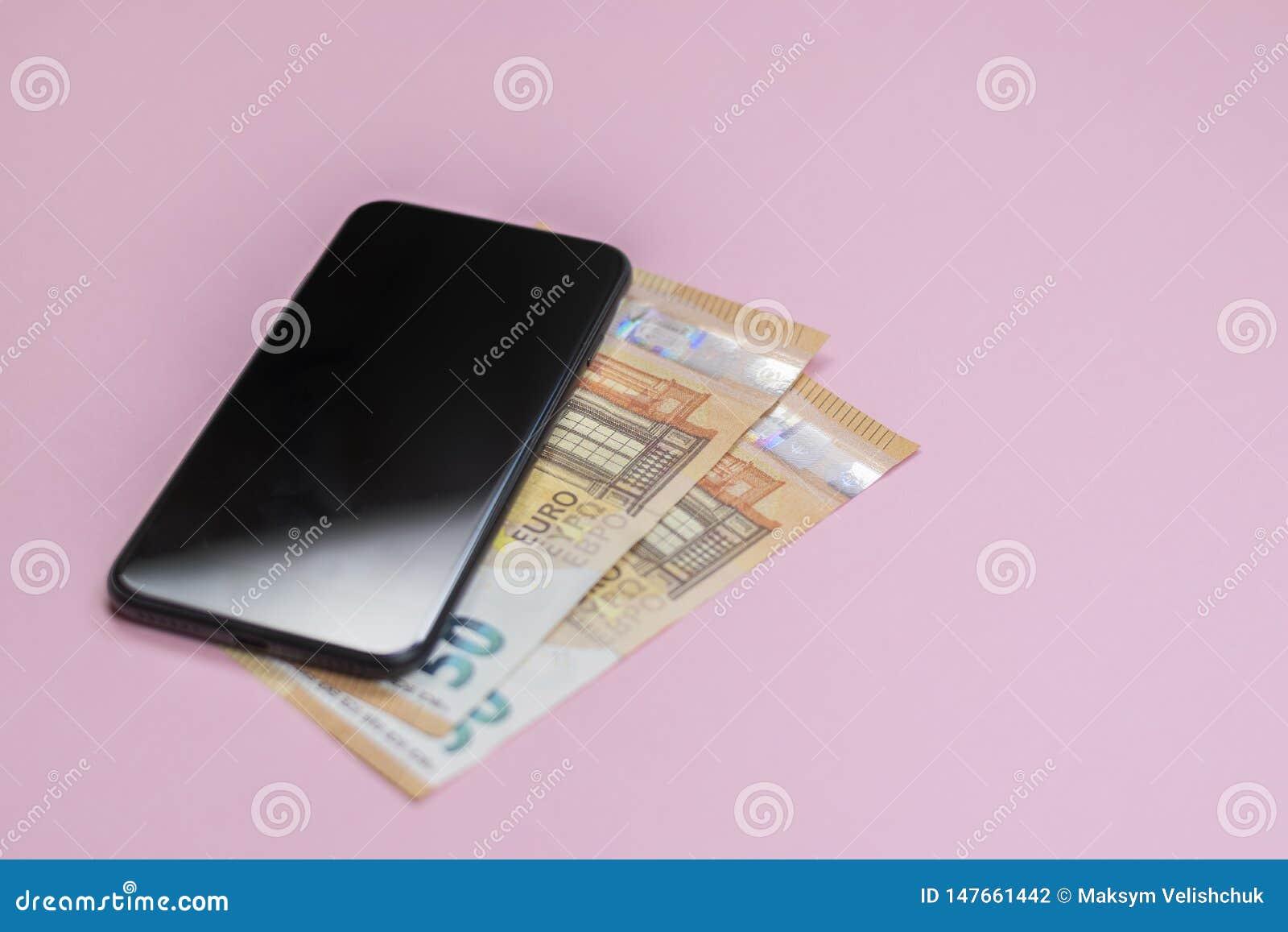 Close-up van smartphone met geld op een roze achtergrond