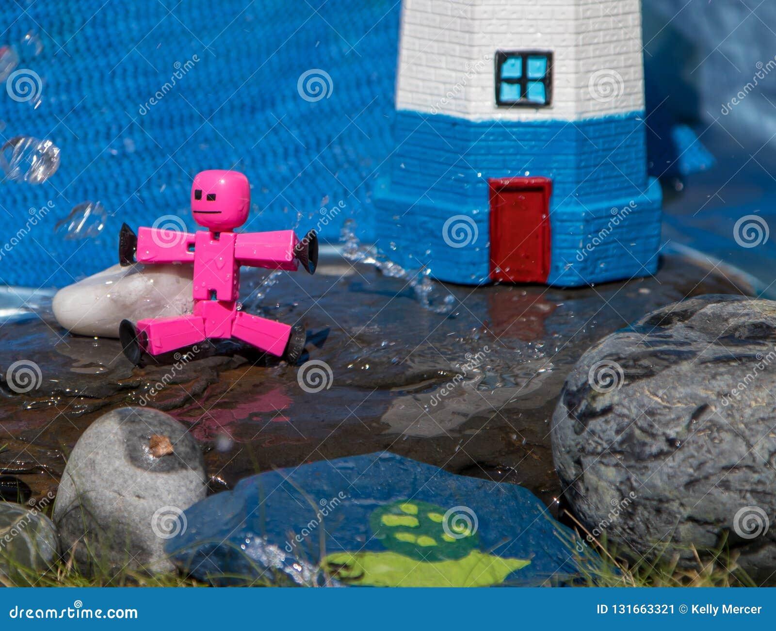Close-up van stuk speelgoed stokcijfers die op natte rotsen spelen