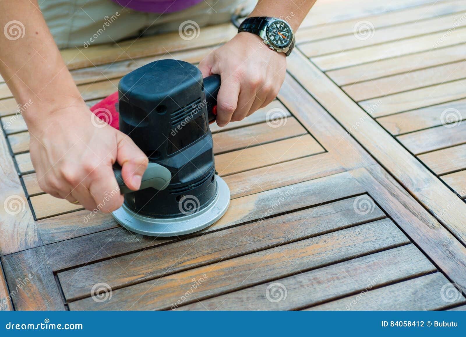 Close-up van timmermans` s handen die met elektrische schuurmachine werken