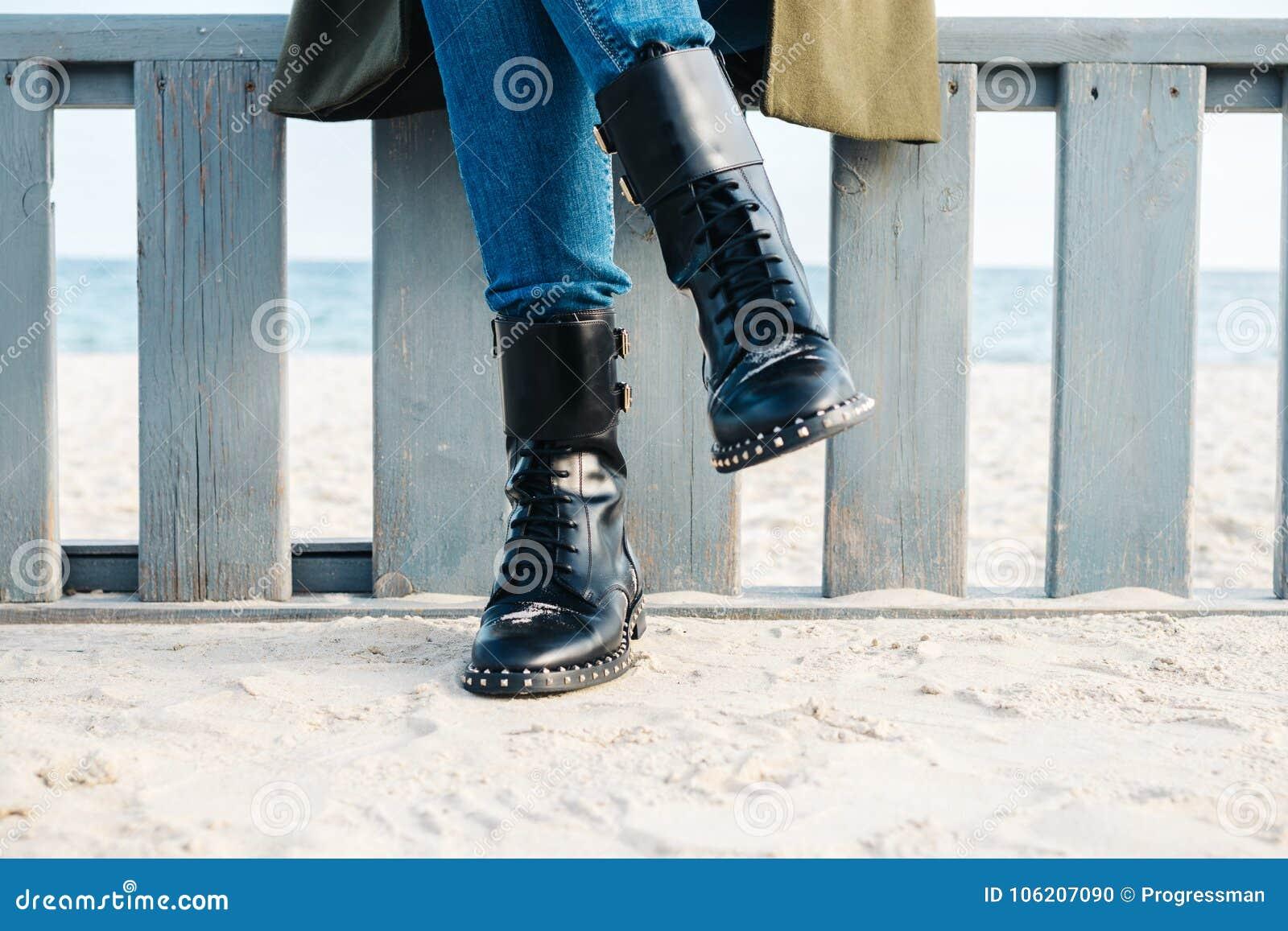 Close-up van vrouwelijke benen in zwarte laarzen en jeans