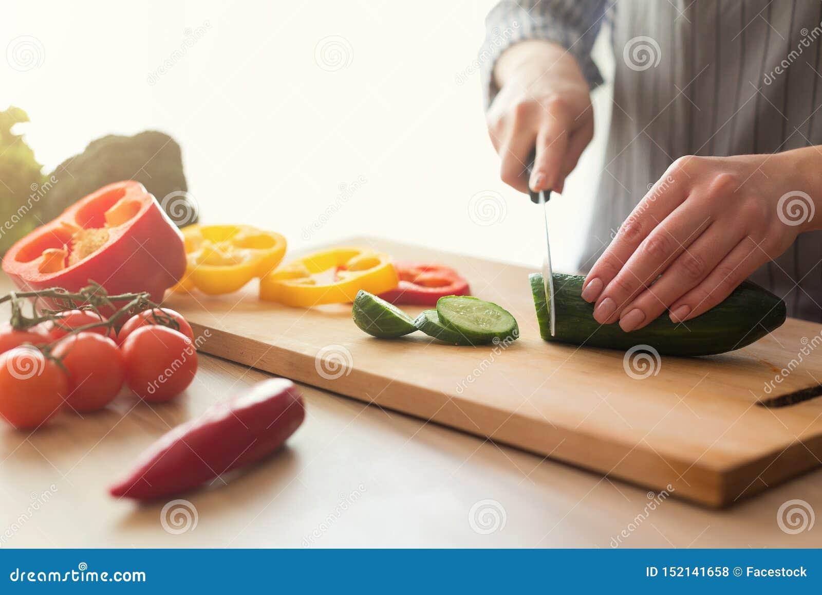 Close-up van vrouwelijke handen die groentensalade in keuken koken