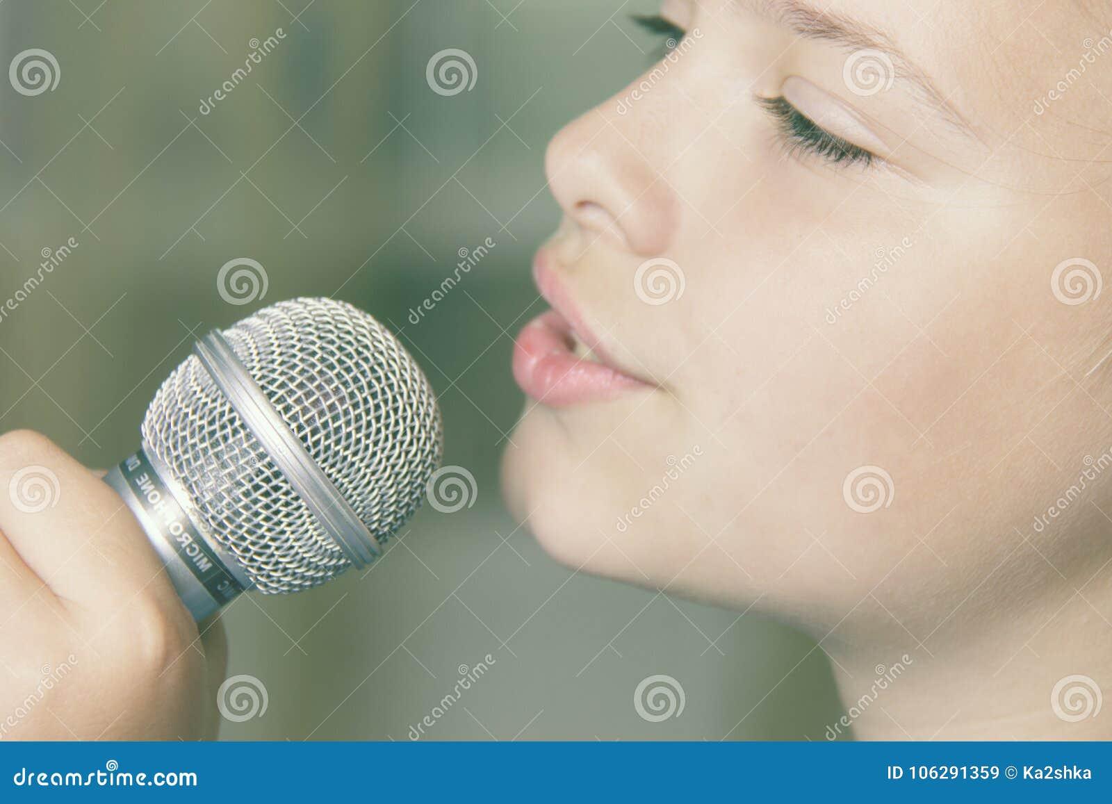 Close-up van zingend Kaukasisch kindmeisje Het jonge meisje zingt emotioneel in de microfoon, houdend het met hand