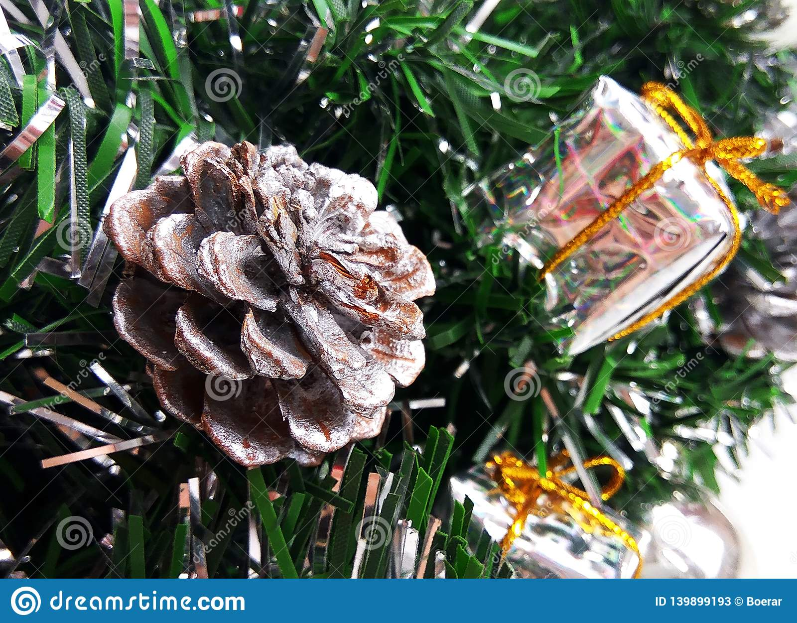 Artificial Christmas tree brunches decorated with silver bauble, toy present boxes and cone