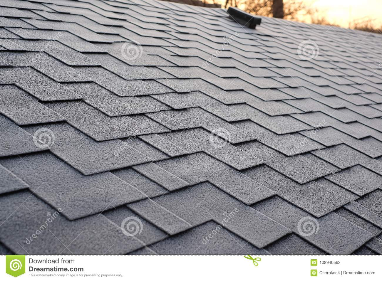 Close up view on Asphalt Roofing Shingles Background. Roof Shingles - Roofing. Shingles roof damage covered with frost.