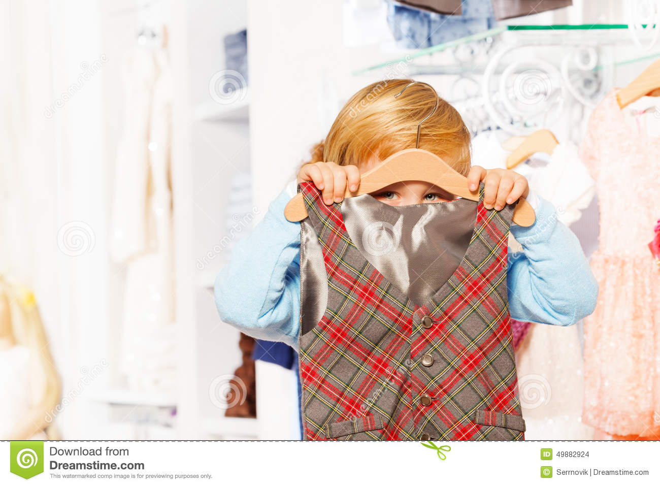 up-view-boy-hiding-behind-hanger-vest-cute-clothes-store-49882924.jpg