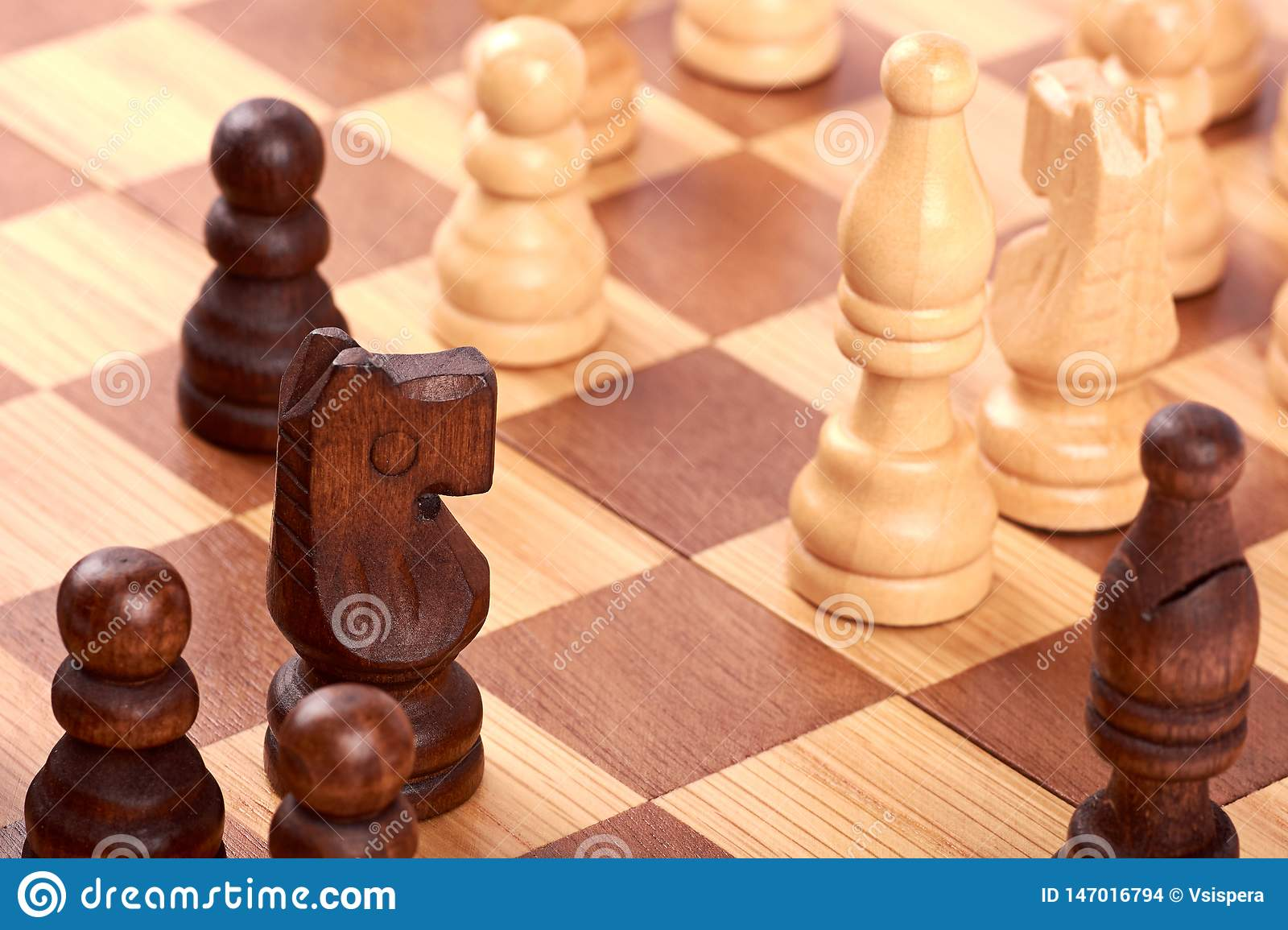 Close-up view of chess game with white and black log pieces on brown chessboard. Fight with horse and pawns