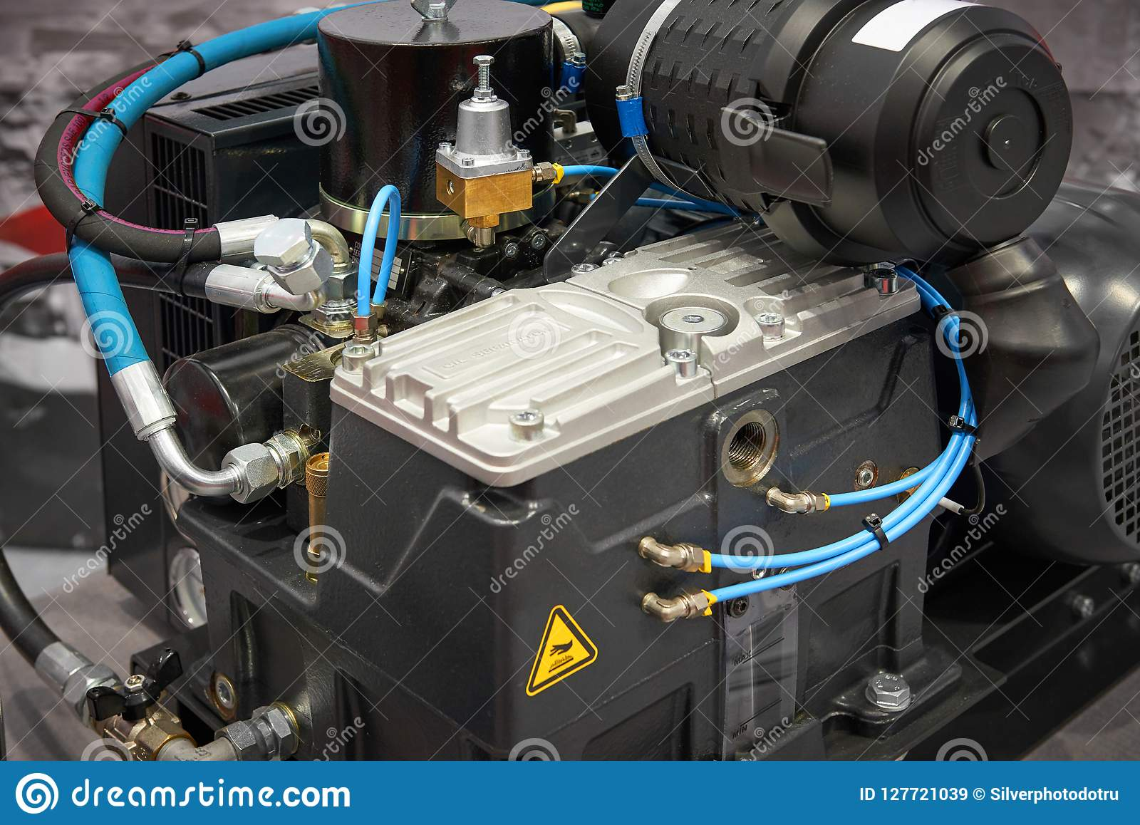 Close up view on clean new air compressor with electric motor, filter, rubber hoses, pneumatic and hydraulic components. Turbo com