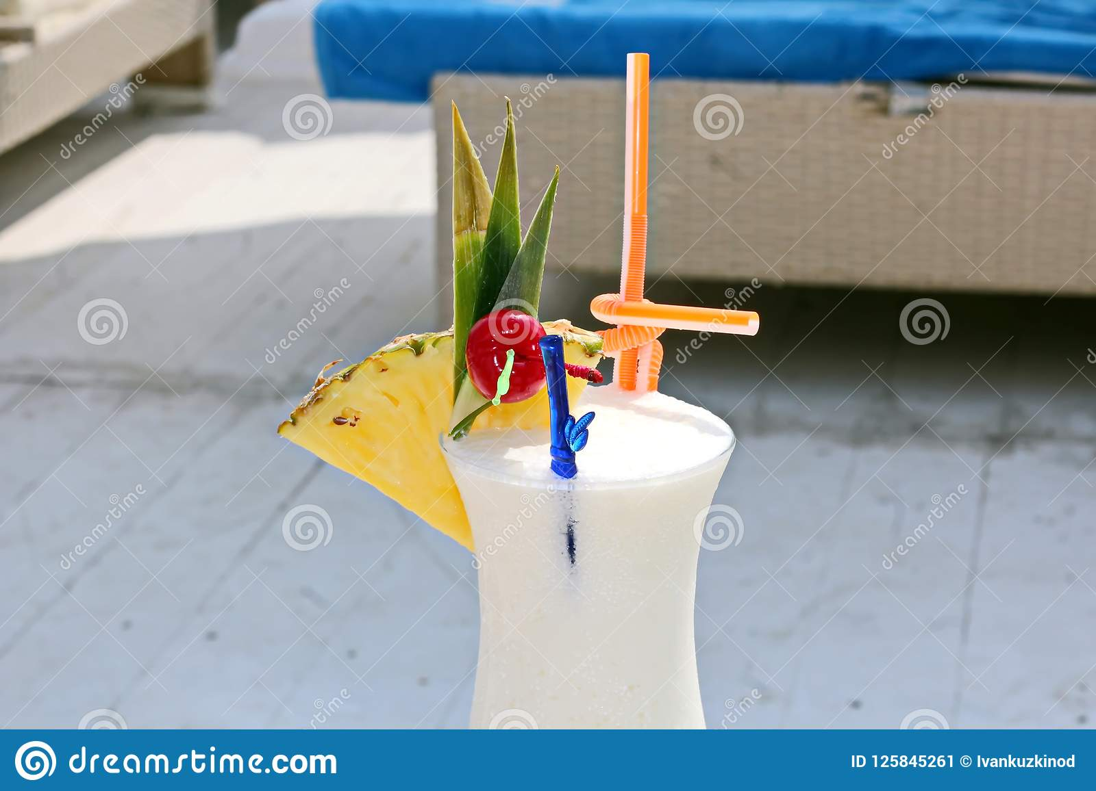 Close-up view of a cold glass of milkshake decorated with tropical fruits and a glass of wine with a lemon inside.