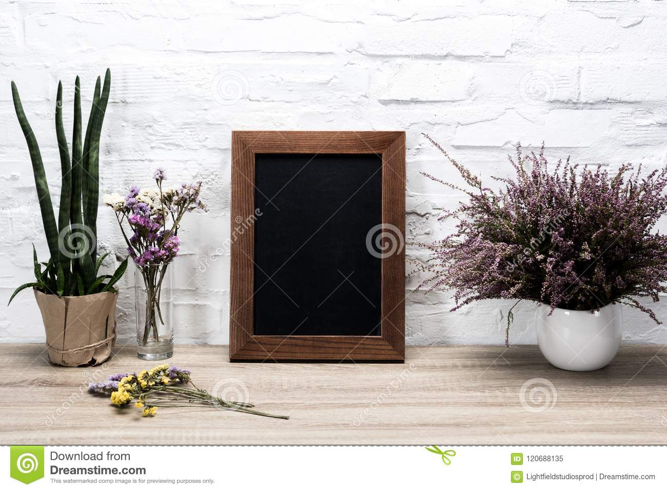 close up view of empty photo frame and lavender flowers in vase