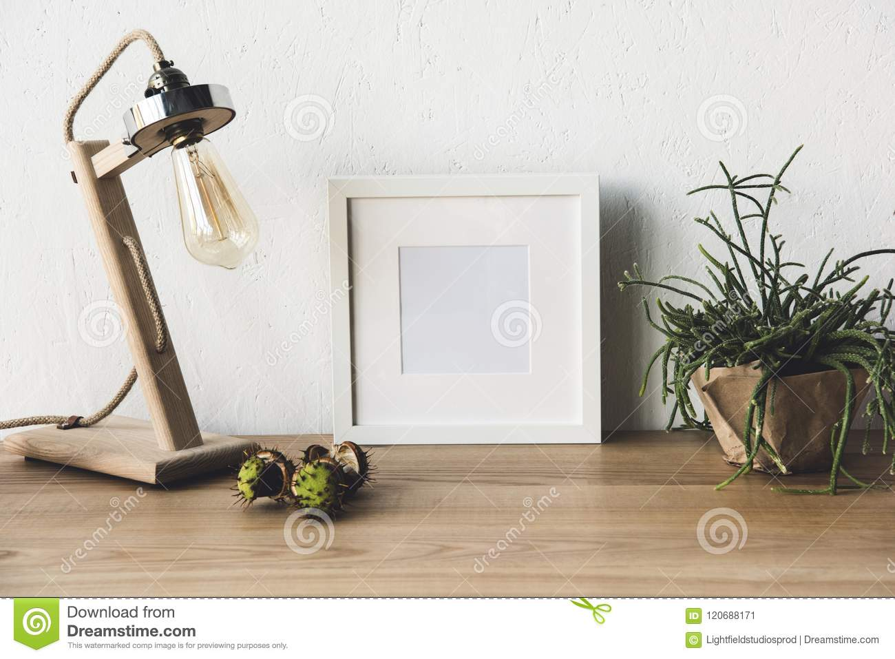 close up view of empty photo frame, table lamp and plant in flowerpot