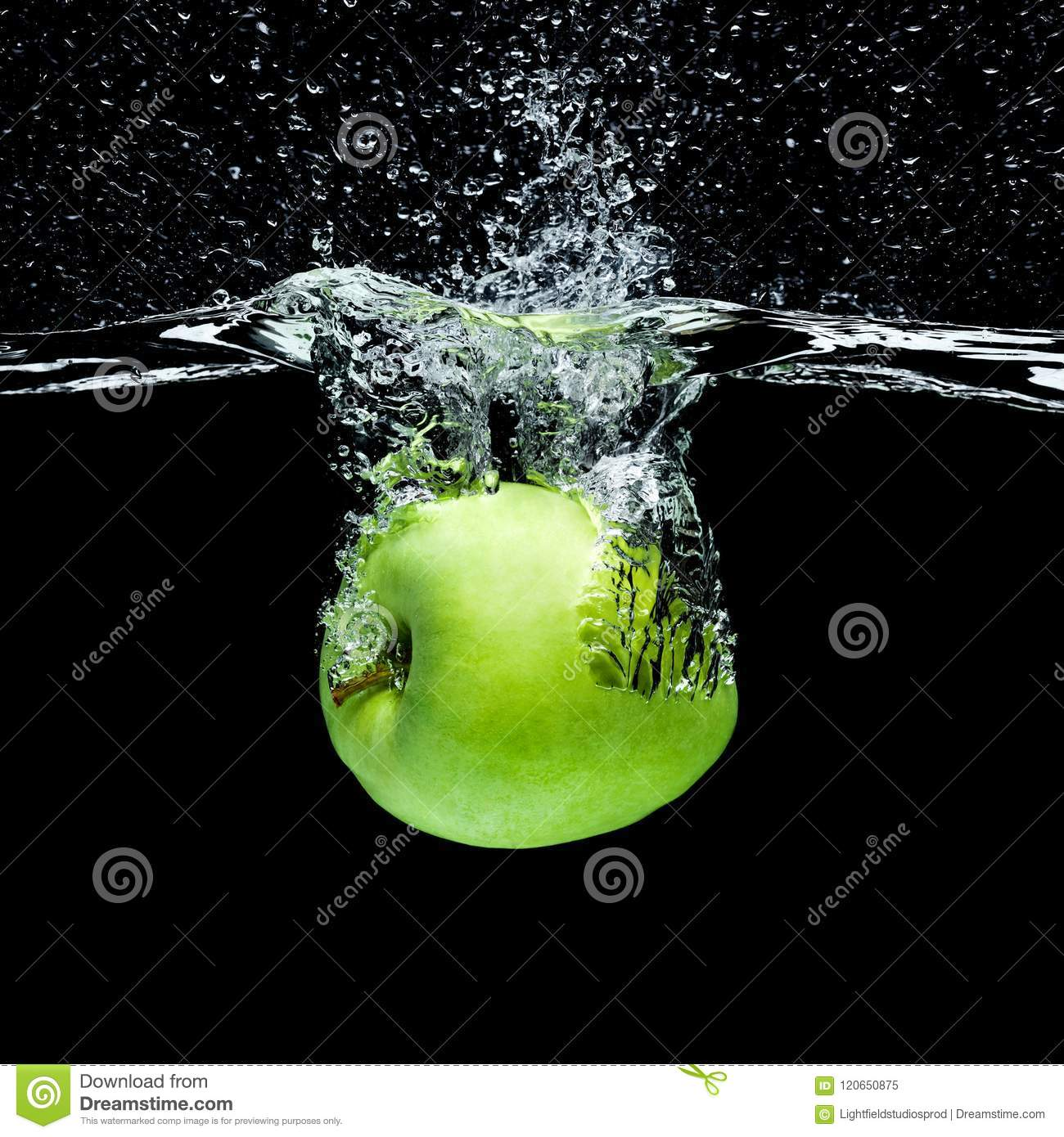 close up view of green apple falling into water