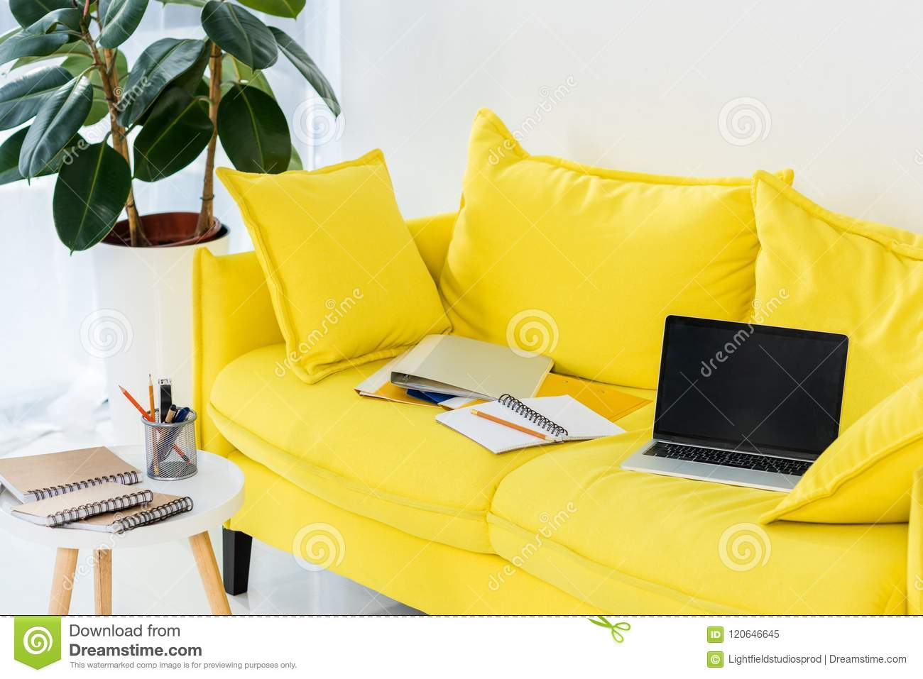 close up view of laptop, notebooks and folders on yellow sofa