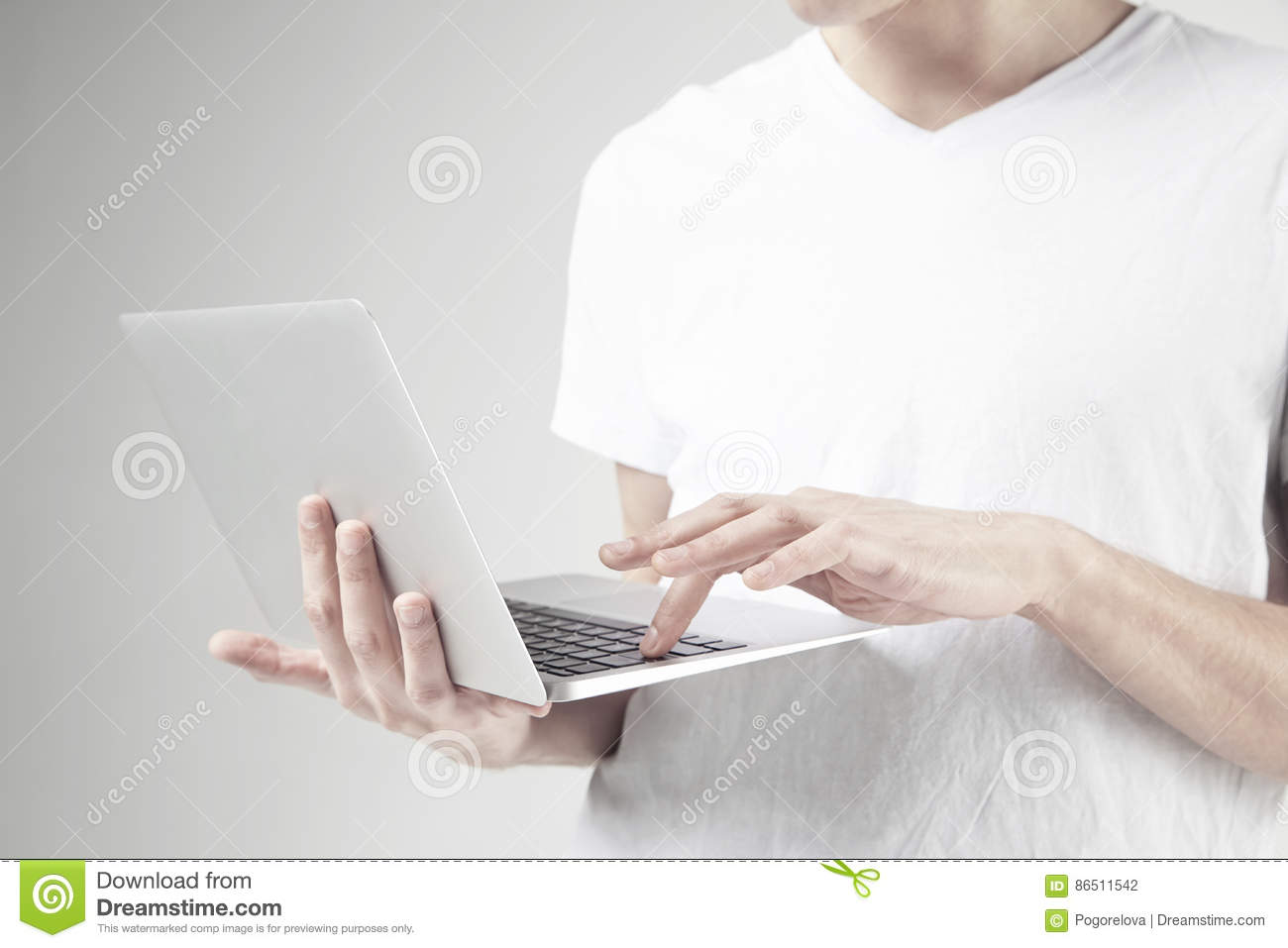 Close-up view of modern laptop in man`s hands, guy wearing white t-shirt, working on portable computer. White background in studio