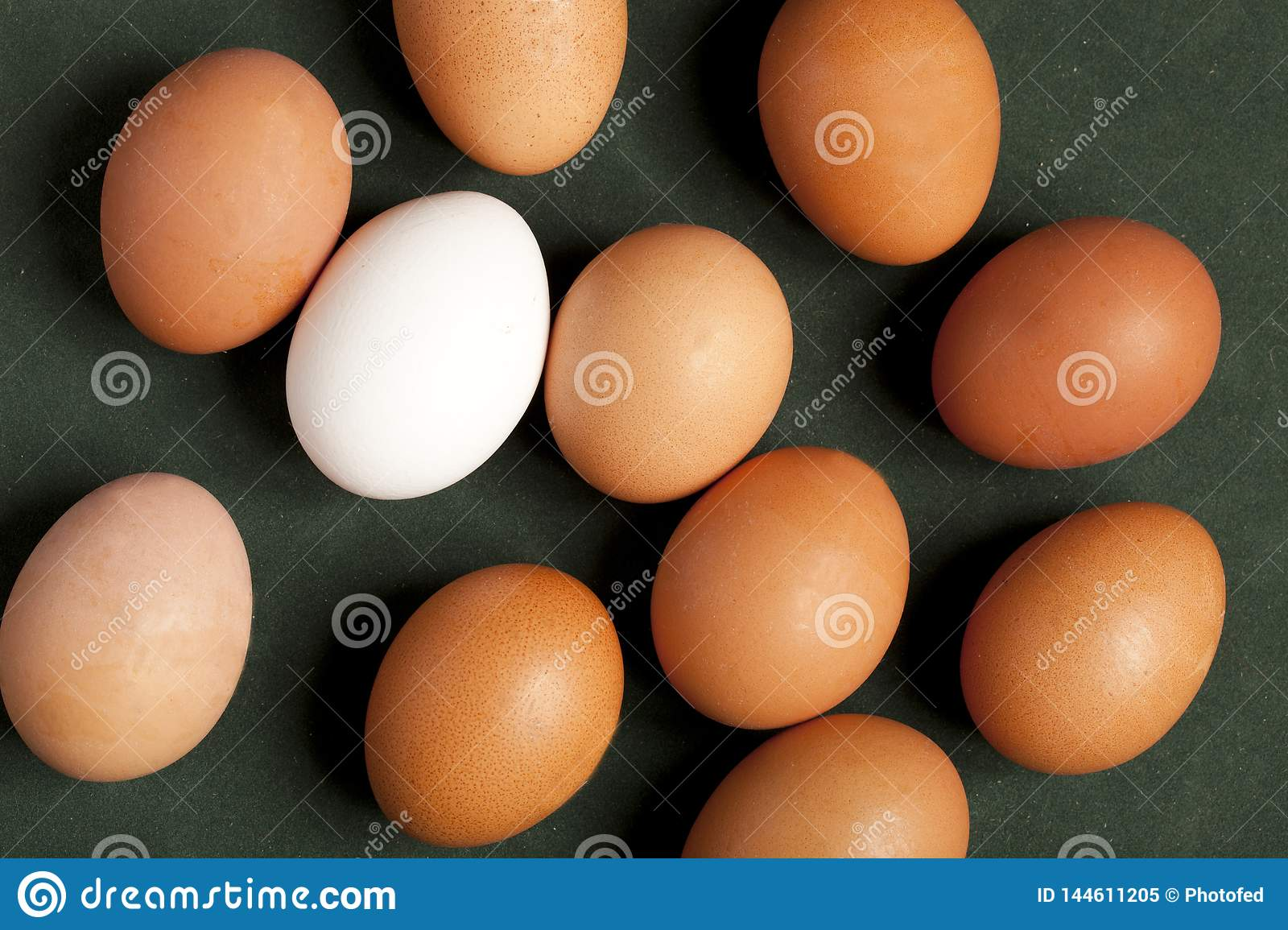 Close-up view of raw chicken eggs in box, egg white, egg brown on green background.