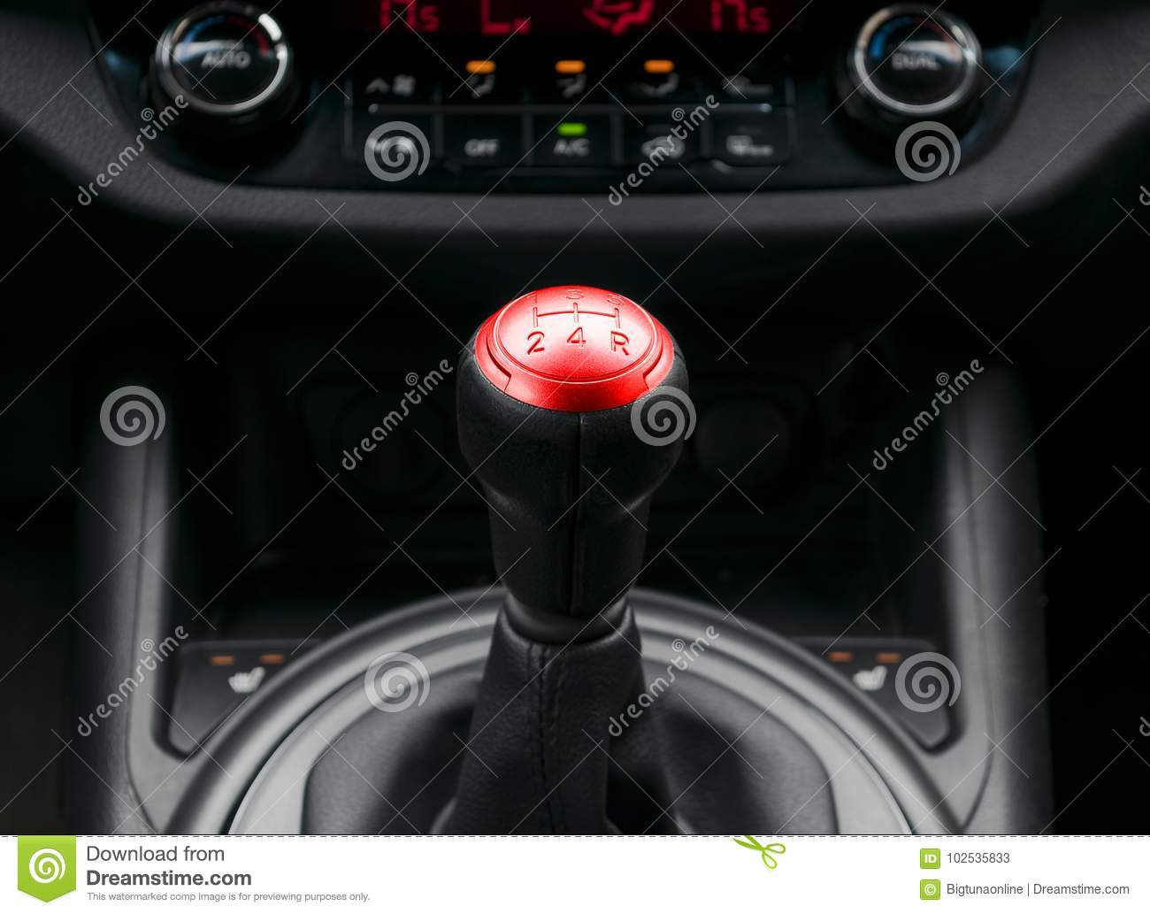 Close up view of a red gear lever shift, manual gearbox, car interior details.