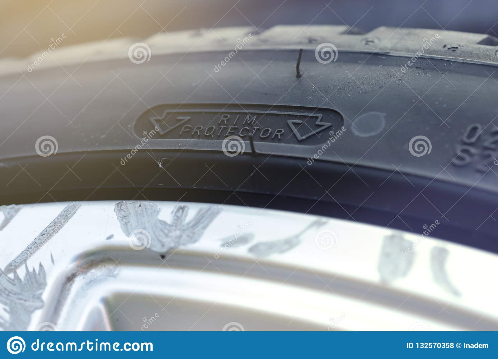 rim protection feature at the sidewall of a high perfomance car tire mounted on a scraped aluminum rim