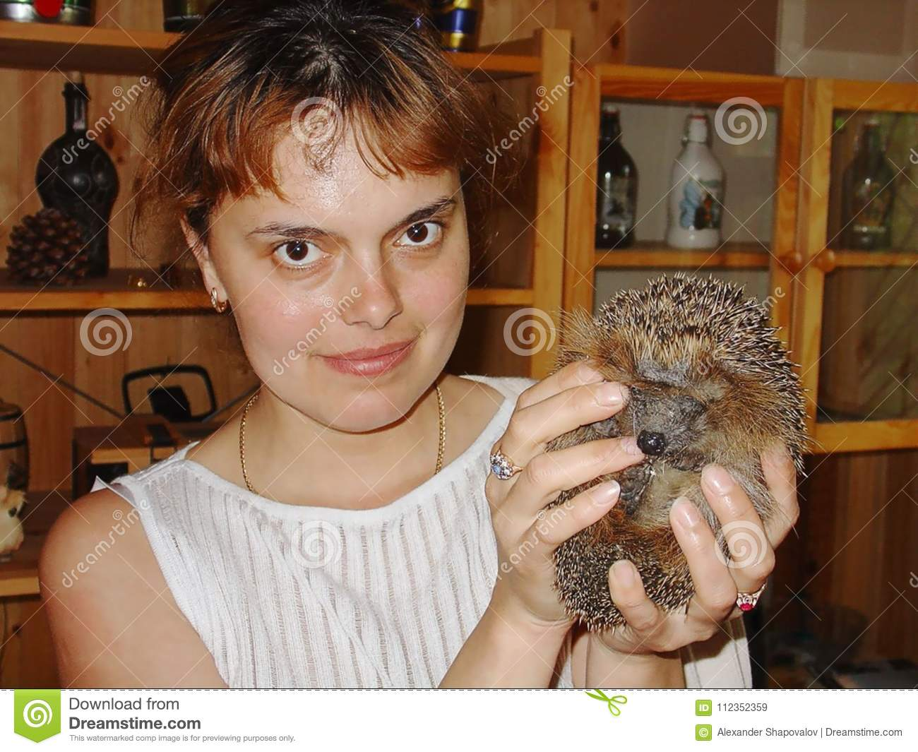 Close up view of a smiling woman holding cute hedgehog in hands.