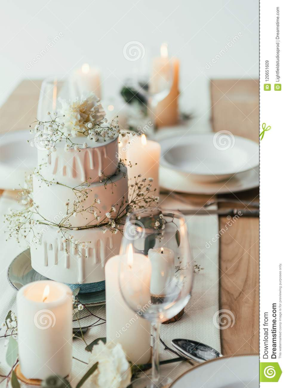 close up view of stylish table setting with candles and wedding cake