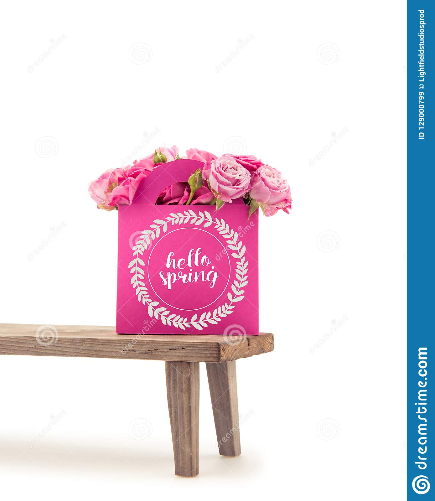 Close-up view of tender blooming rose flowers in pink paper bag with HELLO SPRING lettering on wooden bench