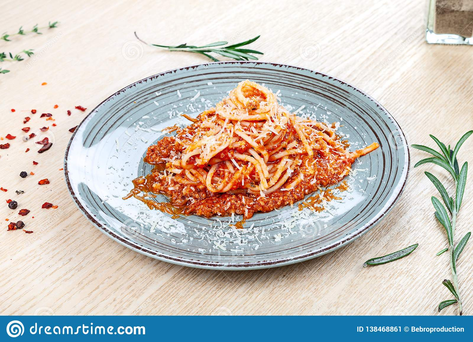 Close up view on traditional italian pasta with cherry tomato, herbs and spices on wooden background.