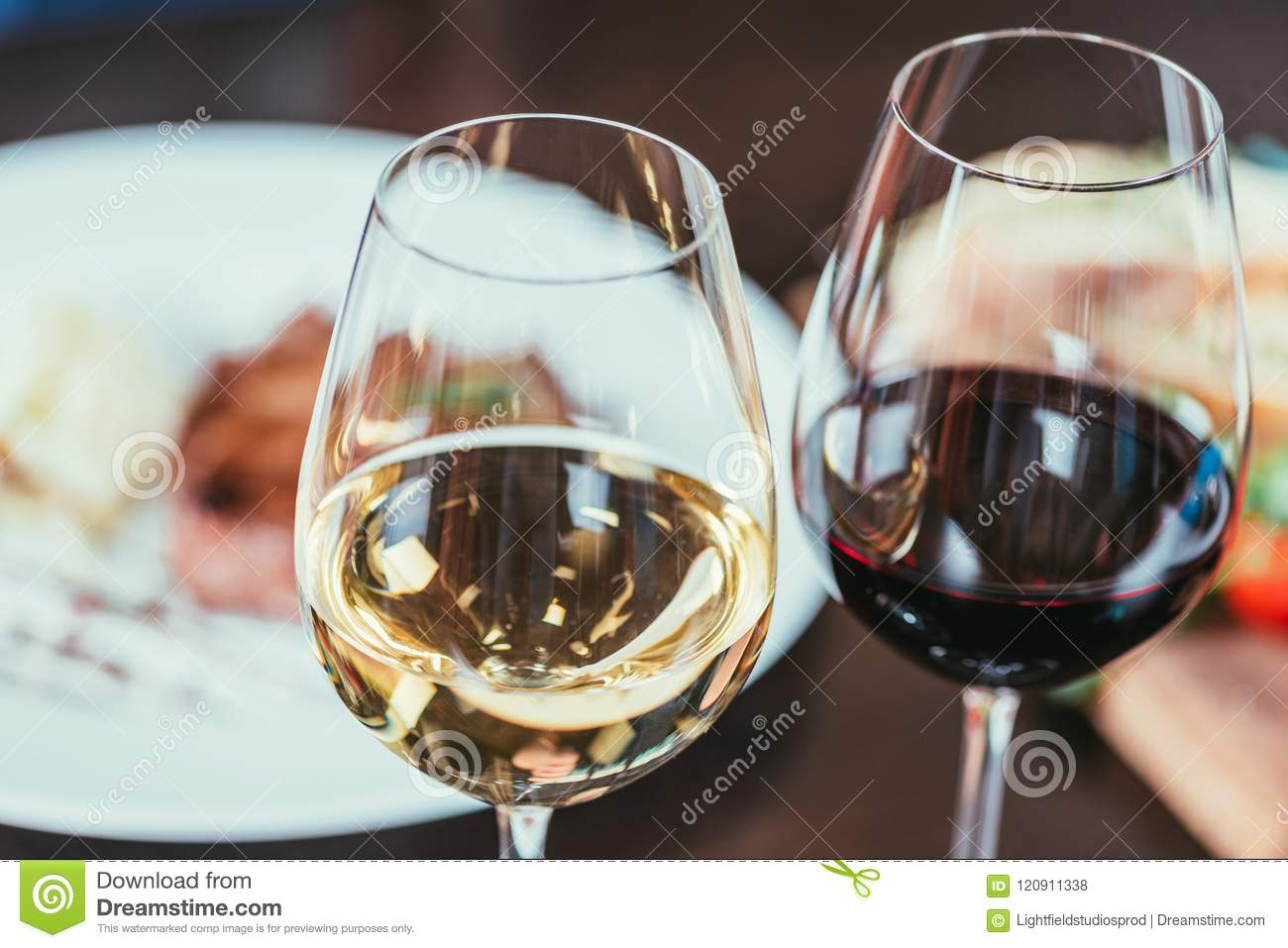 close-up view of two glasses with red and white wine on table