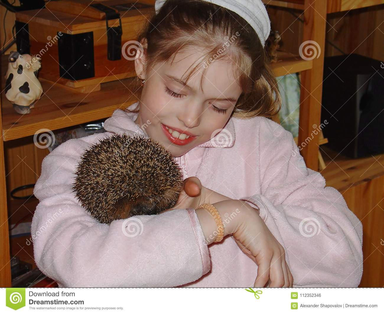 Close up view of a young girl holding a cute hedgehog and smiling.