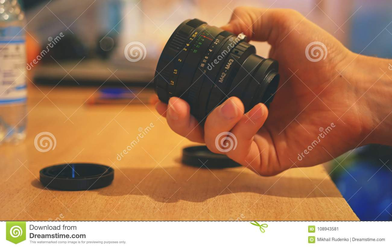Close up vintage camera lens in the hands
