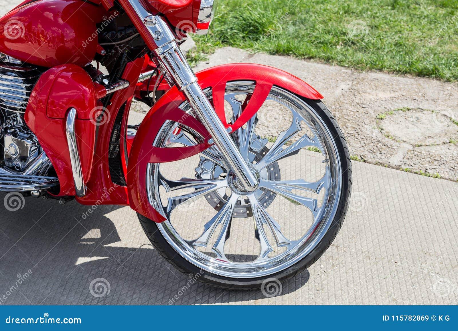 Close-up voordeel van retro douanemotorfiets Het glanzende wiel van de chroom uitstekende fiets met rood stootkussen
